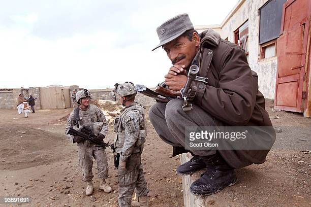 A police officer with the Afghan National Police stands guard with US soldiers as Brig Gen Dowlat Kahn provincial head of the for Paktika Province...