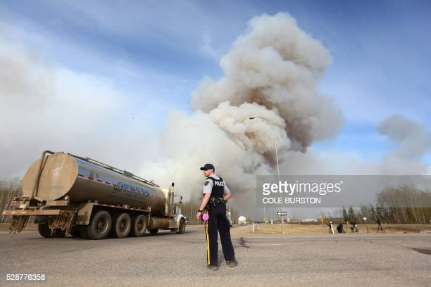 A police officer works a road block on Highway 63 near Fort McMurray Alberta on May 6 2016 Canadian police led convoys of cars through the burning...