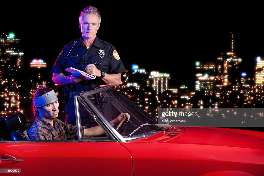 Police Officer Writing a Citation at Night : Stock Photo