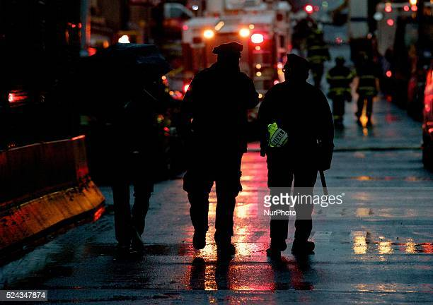 Police officers accompany a resident that lives within the area where a gas leak explosion knocked down two buildings in East Harlem, New York that...