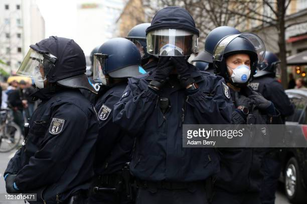 Police officers adjusts his face mask while monitoring a demonstration against restrictions on public life designed to stem the spread of the...