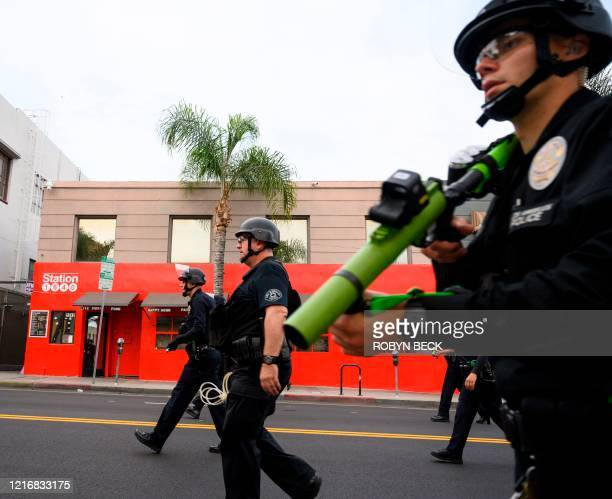 Police officers advance up a main street in Hollywood California as peaceful protests and looters broke into stores in Hollywood California June 1...