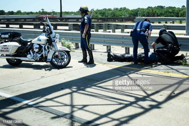 Police Officers aid an officer involved in an accident while escorting a motorcade with US President Donald Trump from Chennault International...
