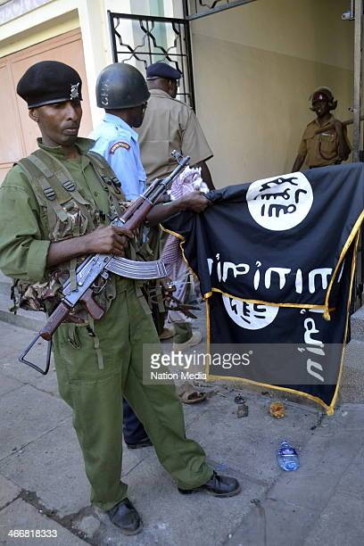 Police officers aisplay weapons and flags seized from youth at Masjid Musa mosque on February 2 2014 in Mombasa Kenya Police raided the mosque saying...