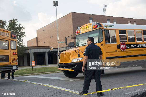 Police officers allow a school bus to depart Fern Creek High School following a shooting incident September 30 2014 in Louisville Kentucky Police say...