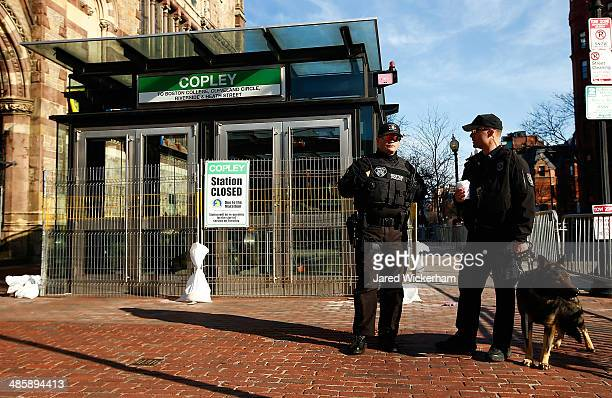 Police officers and a K9 unit patrol Boylston Street next to the closed down MBTA Copley station prior to the start of the 2014 BAA Boston Marathon...