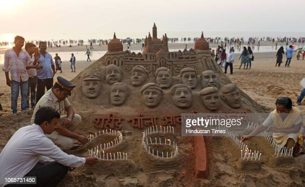 Police officers and a lady Sand Artist light the candles in front of sand art which is tribute to 26/11 victims at Juhu Beach on the occasion the...