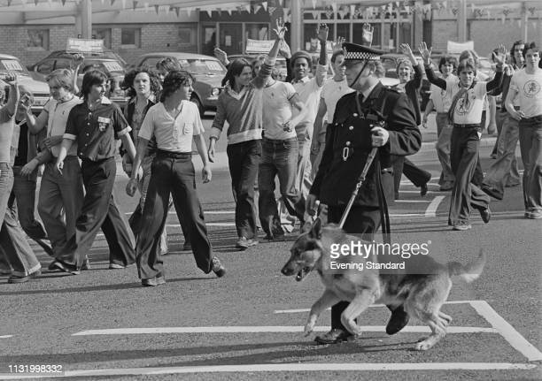 Police officers and a police dog Millwall FC supporters keep Millwall FC fans under control before a match, UK, 19th August 1975.