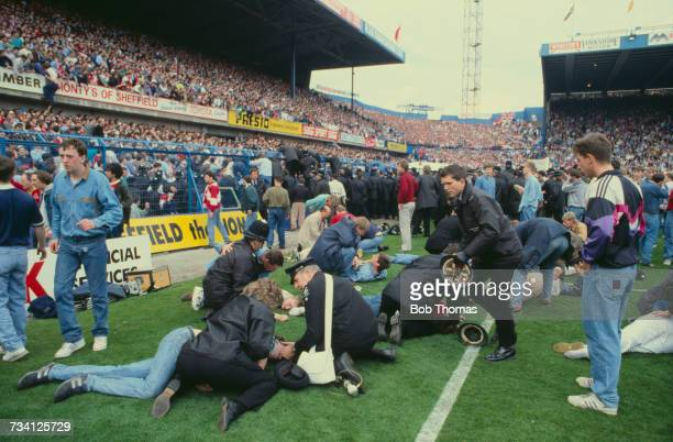 Police officers and a St John Ambulance volunteer attend to casualties on the pitch at Hillsborough football stadium in Sheffield after a human crush...