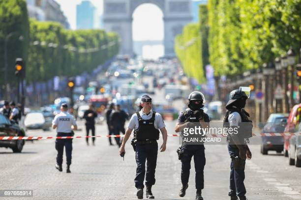 TOPSHOT Police officers and antiriot police officers patrol the ChampsElysees avenue on June 19 2017 on the ChampsElysees avenue in Paris after a car...