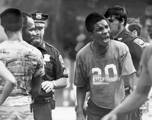 Police officers and bystanders listen as a young man voices a grievance at the scene of a disturbance in Boston's Roxbury neighborhood on Jun 23 1976...