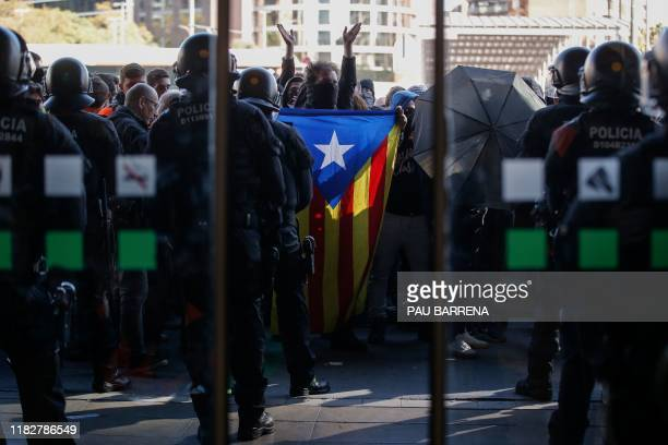 Police officers and Catalan regional police 'Mossos D'Esquadra' officers stand guard at the entrance of the Barcelona Sants railway station as...