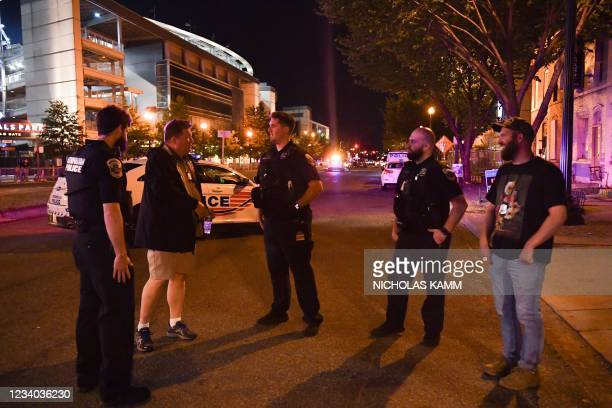 Police officers and detectives stand in a street near the Nationals Park stadium as the game between the Washington Nationals and the San Diego...