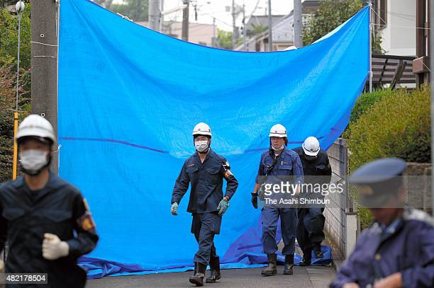 Police officers and fire fighters investigate the light airplane crash site on July 27, 2015 in Chofu, Tokyo, Japan. Police recovered the engine to...
