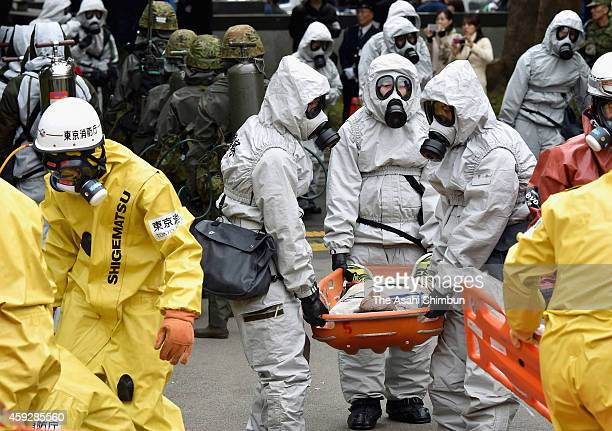 Police officers and fire fighters wearing protection gears takes part in a large scale antiterror exercise on November 20 2014 in Tokyo Japan The...