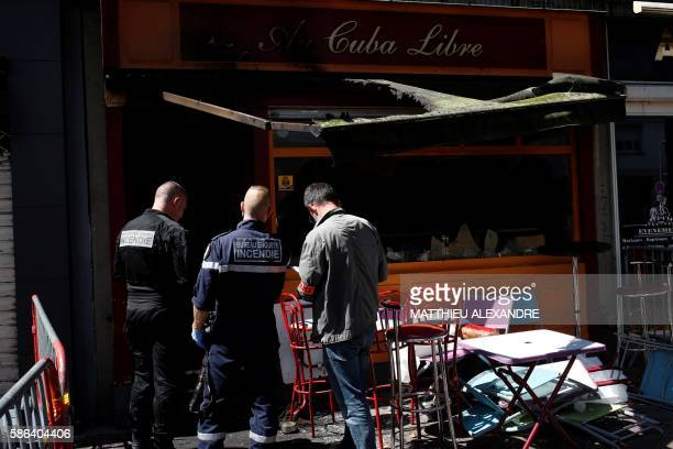 TOPSHOT Police officers and firefighters inspect the damaged Au Cuba Libre bar in Rouen northern France on August 6 after a fire broke out overnight...