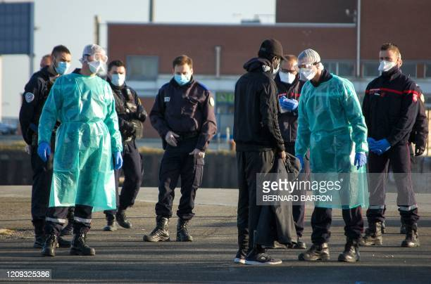 Police officers and firefighters wearing protective equipment speak with a migrant in Calais' harbour, after he was apprehended off the coast of...