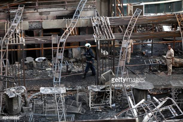 Police officers and firemen inspect the burning building after a fire broke out at a rooftop restaurant in Mumbai India on December 29 2017 At least...