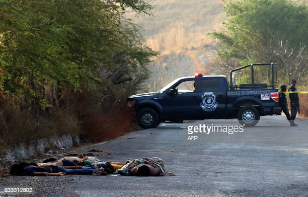 TOPSHOT Police officers and forensic personnel work at the place where six corpses were found on a road in Mochitlan Guerrero State Mexico on...