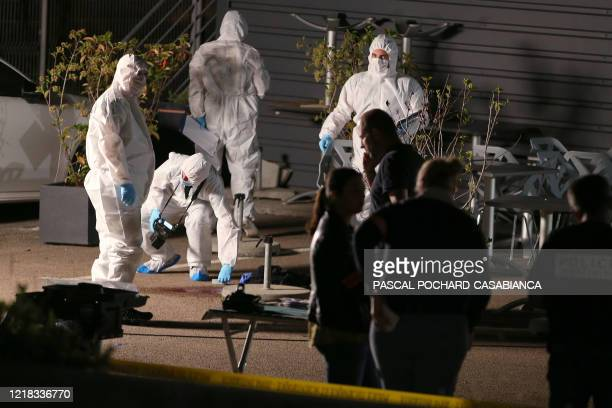 Police officers and forensics search for evidences on a crime scene where two men were injured by gun shots on a terrace of a restaurant overnight on...