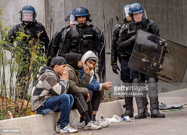 Police officers and gendarmes stand guard during the eviction of migrants from a camp site in Calais northern France on September 21 2015 Thousands...