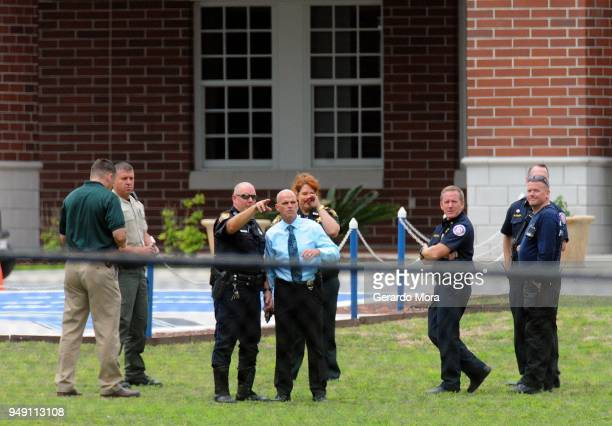 Police officers and local authorities stand in front of Forest High School after a school shooting on April 20 2018 in Ocala Florida It was reported...
