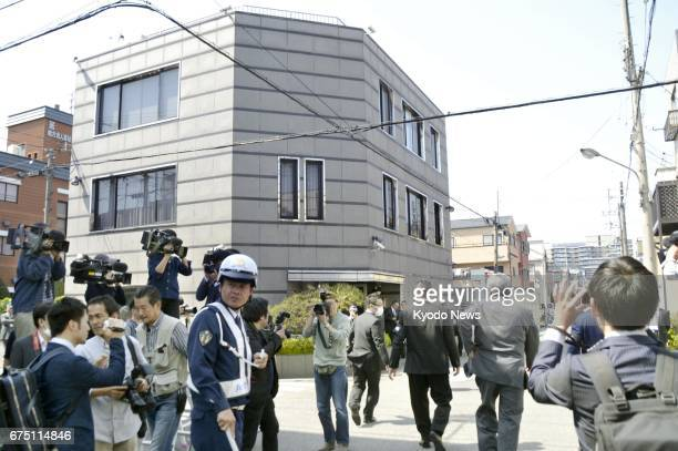 Police officers and media personnel gather around an office building in Amagasaki in Hyogo Prefecture western Japan on April 30 where a meeting was...