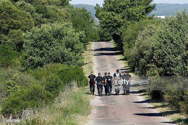 Police officers and members of a fire brigade participate on June 28 2011 in RoquebrunesurArgens in a massive search for murder suspect Xavier Dupont...