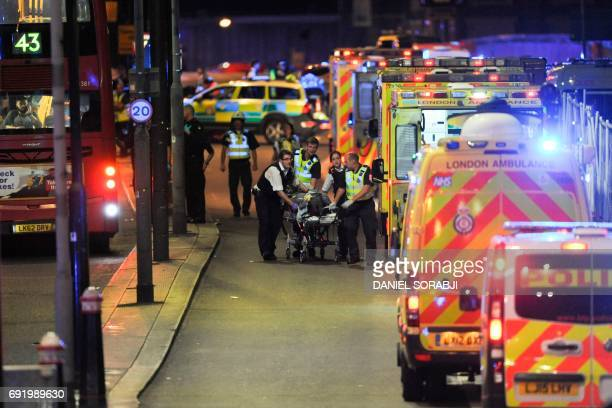 TOPSHOT Police officers and members of the emergency services attend to a person injured in an apparent terror attack on London Bridge in central...