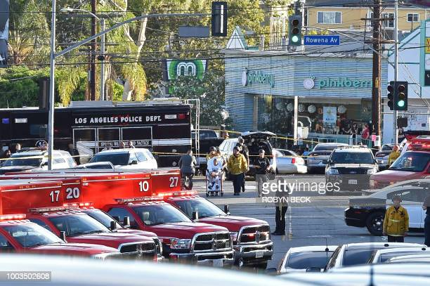Police officers and members of the Los Angeles Fire Department escort a boy on a stretcher after a suspect barricaded inside a Trader Joe's...