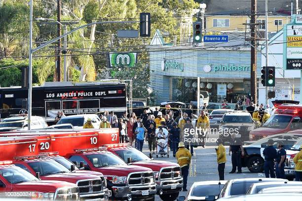 Police officers and members of the Los Angeles Fire Department escort a woman on a stretcher after a suspect barricaded inside a Trader Joe's...