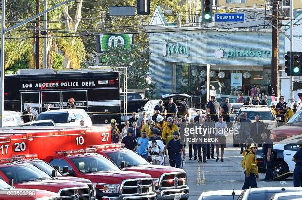 TOPSHOT Police officers and members of the Los Angeles Fire Department escort a woman on a stretcher after a suspect barricaded inside a Trader Joe's...