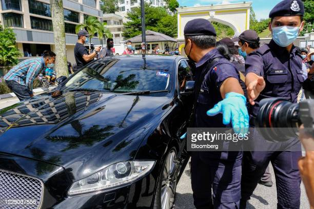 Police officers and members of the media surround a vehicle transporting Anwar Ibrahim founder and president of the People's Justice Party leaves the...