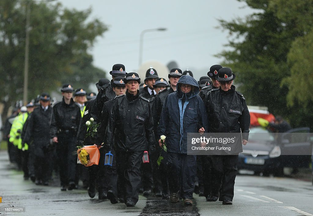 Police officers and members of the public walk to the scene where PC Nicola Hughes and PC Fiona Bone were murdered one week ago, in Mottram on September 25, 2012 in Manchester, England. Members of the public joined police officers in a walk in heavy rain from Hyde police station to the scene of the killings, for a vigil of prayers and reflection. Dale Cregan, 29, appeared before Manchester Magistrates last week accused of four murders, including those of PC Nicola Hughes and PC Fiona Bone on September 18, and also in two separate attacks earlier this year on Mark Short and his father David Short. Cregan is also being charged with an additional four counts of attempted murder.