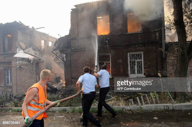 Police officers and municipal workers attempt to extinguish a fire that engulfed a residential area in the southern Russian city of RostovonDon on...