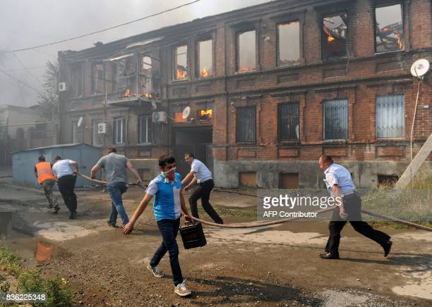 Police officers and municipal workers run with a hose as they attempt to extinguish a fire that engulfed a residential area in the southern Russian...
