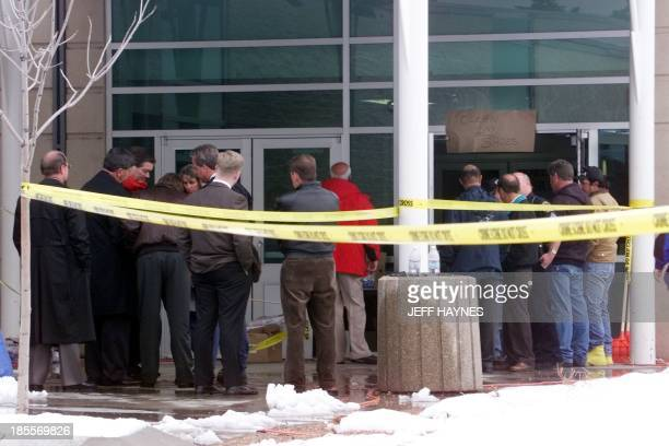 Police officers and officials stand in front of Columbine High School in Littleton CO 22 April the site where fourteen students and one teacher were...