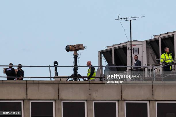 Police officers and other people stand near equipment on the rooftop of a building as the runway is reopened at London Gatwick Airport on December 21...