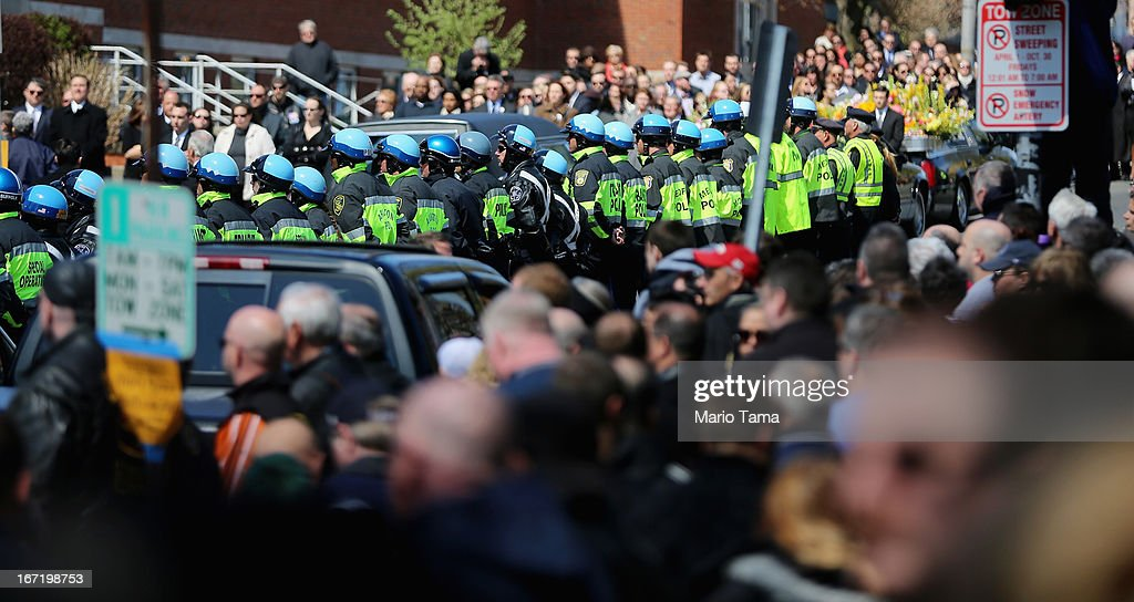 Police officers and others gather outside the funeral for 29-year-old Krystle Campbell, who was one of three people killed in the Boston Marathon bombings, on April 22, 2013 in Medford, Massachusetts. The 29-year-old restaurant manager was raised in Medford. Massachusetts Gov. Deval Patrick has asked residents to observe a moment of silence at the time of the first explosion at 2:50 p.m. this afternoon.