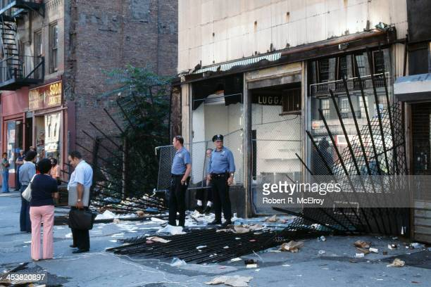 Police officers and passersby stand in front of a damaged store front looted in the wake of the New York City blackout Brooklyn New York New York...