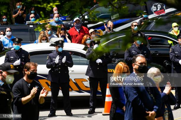 Police officers and residents line the street to pay their respects during the funeral of Glen Ridge Police Officer Charles Roberts after he passed...