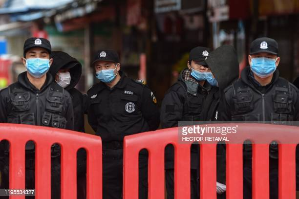 A police officers and security guards stand outside the Huanan Seafood Wholesale Market where the coronavirus was detected in Wuhan on January 24...