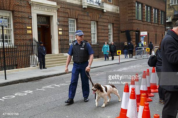 Police officers and sniffer dogs carry out security checks outside St Mary's Hospital ahead of the Duchess of Cambridge departure with her new born...