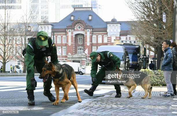Police officers and sniffer dogs search for any suspicious materials such as explosives on the streets near JR Tokyo Station the finishing point of...