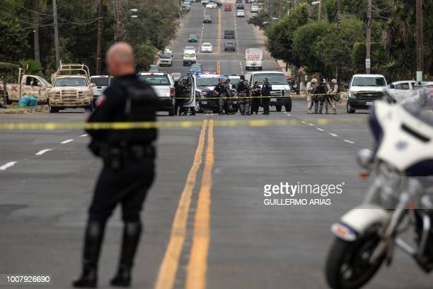 Police officers and soliders block a road near a house where a shooting and hostage situation took place in Playas de Tijuana Tijuana Baja California...
