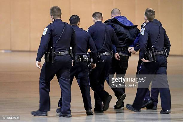 Police officers and US Secret Service take a man away in handcuffs from a campaign rally for Republican presidential nominee Donald Trump at the...