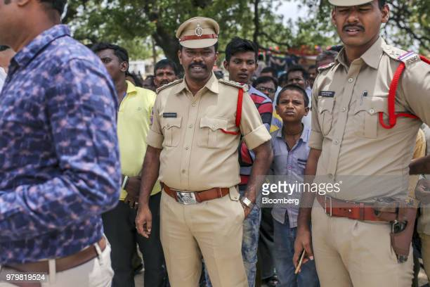 Police officers and villagers look on after attending an event to raise awareness on fake news in Balgera village in the district of Gadwal Telangana...