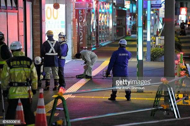 Police officers and workers investigate a slight gradation on the sidewalk is seen in front of JR Hakata Station early in the morning after the...