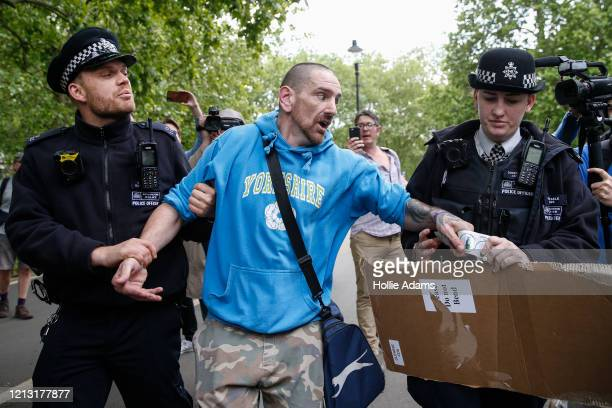Police officers apprehend a protester as people demonstrate against the coronavirus lockdown in Hyde Park on May 16 2020 in London United Kingdom The...