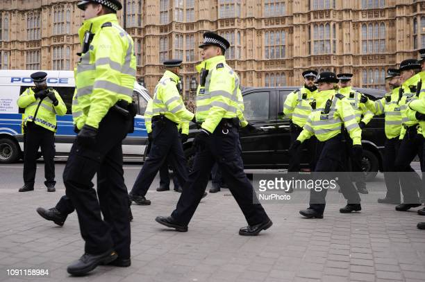 Police officers approach Brexit supporters and opponents demonstrating opposite the Houses of Parliament in London, England, on January 29, 2019. In...